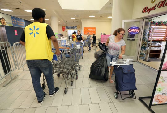 Marilyn Cruz of the Bronx hauls her Walmart purchases from White Plains store Aug. 3, 2018. Cruz said she spent $178 for $628 worth of goods. She plans on selling everything at a flea market. With all remaining items for sale marked down 75%, shopper were able to find bargains as the shelves emptied. The store closes its doors on Aug. 10th.