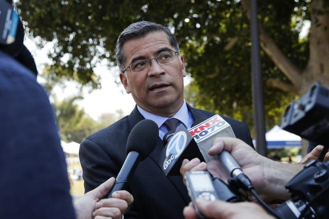 California Attorney General Xavier Becerra talks to reporters after a news conference at University of California, Los Angeles Thursday, Aug. 2, 2018. Becerra spoke about his efforts to fight the Trump administration's proposal to weaken car efficiency fuel standards.