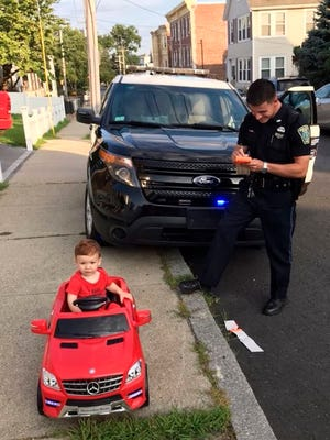 """In this July 31, 2018 photo, Grayson Salerno, 1, is pulled over for driving without a license, but he got off with a """"cuteness warning"""" in Malden, Mass. Police in the Boston suburb said they staged the traffic stop after spotting Salerno driving a red toy Mercedes convertible along a sidewalk."""