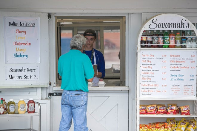 Austin Wyre takes a customer's order at Savannah's in the back parking lot of the Prices Corner Shopping Center.