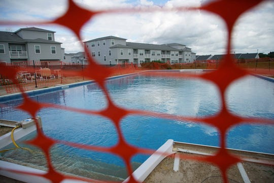 A swimming pool was built and filled in April with the assurance it would be finished by Memorial Day. It is still unfinished, with what residents feel is an unsafe construction fence.