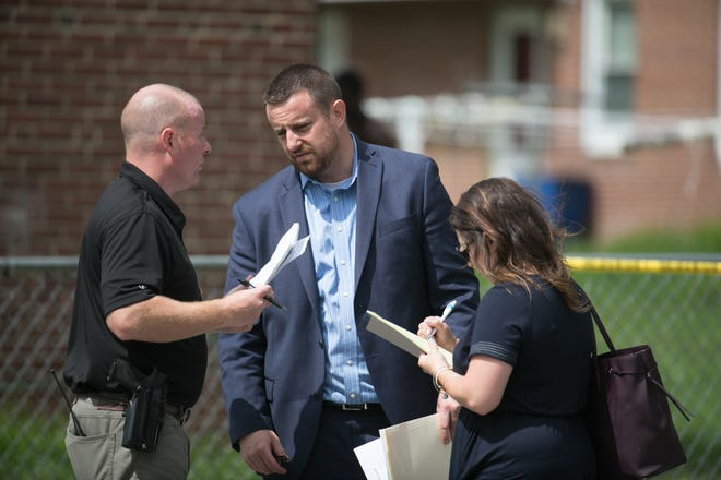 State prosecutor Mark Denney, middle, speaks with investigators.