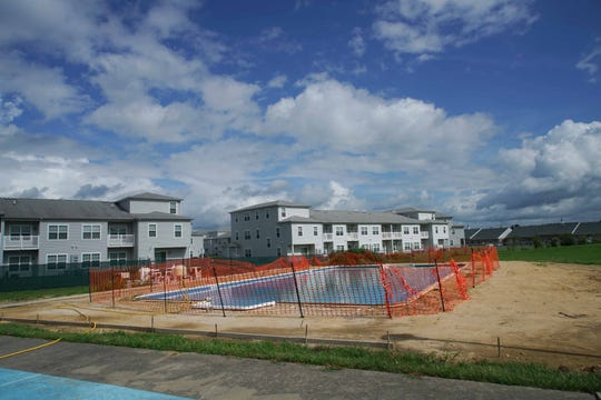 A swimming pool surrounded by a construction fence sits unfinished near the Bon Ayre clubhouse. Nearby neighboring apartments loom on the other side of the 55 and older community.