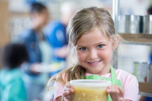 Young Girl Volunteers At Soup Kitchen