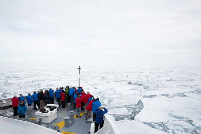 Passengers on a Silversea ship gaze out over polar ice during an Arctic expedition.