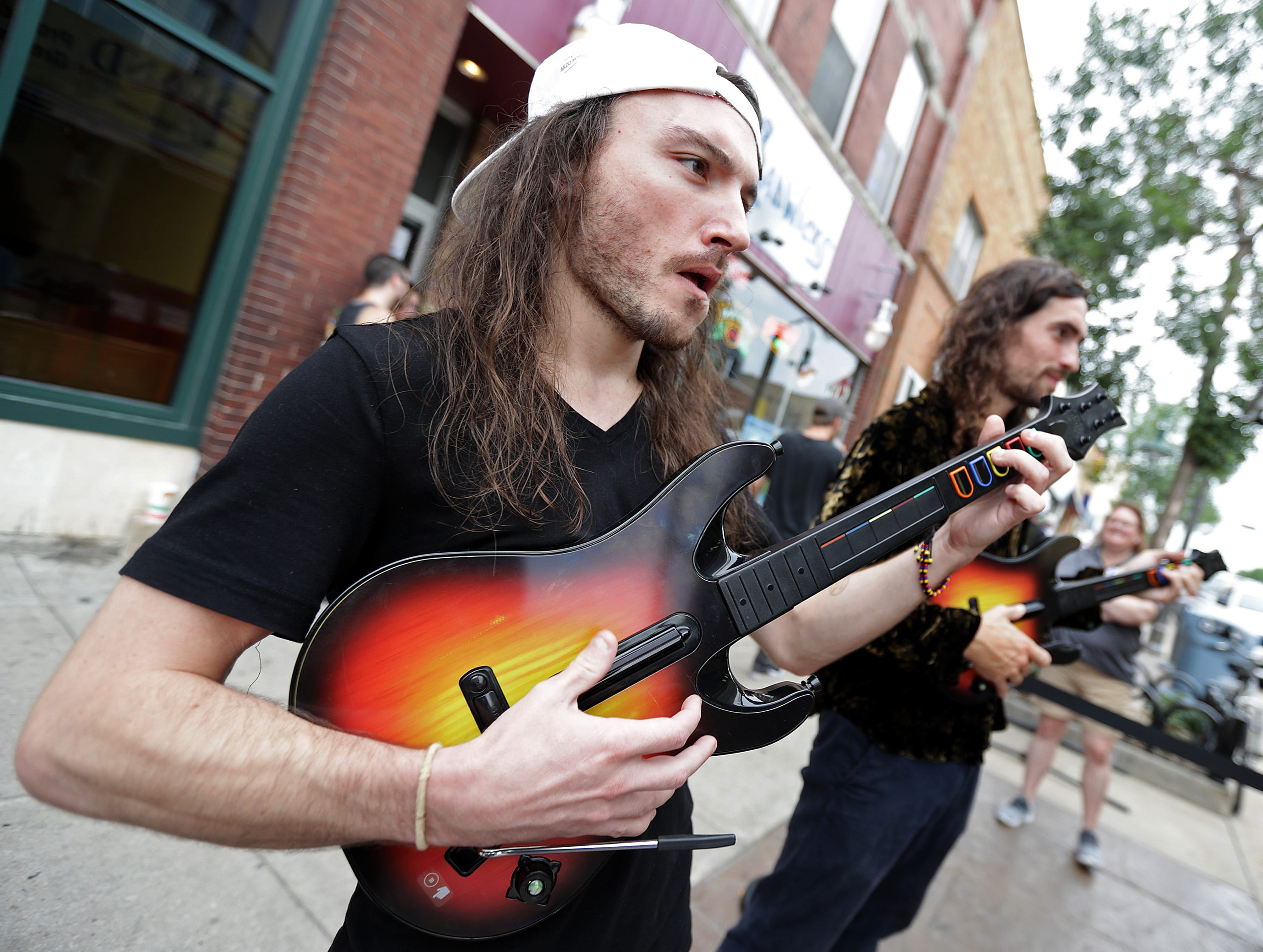 Cameron Clark, left, and James Weishar, from the band C2 and The Brothers Reed, stop to play sidewalk Rockband during the Mile of Music festival Friday, August 3, 2018, in Appleton, Wis. 