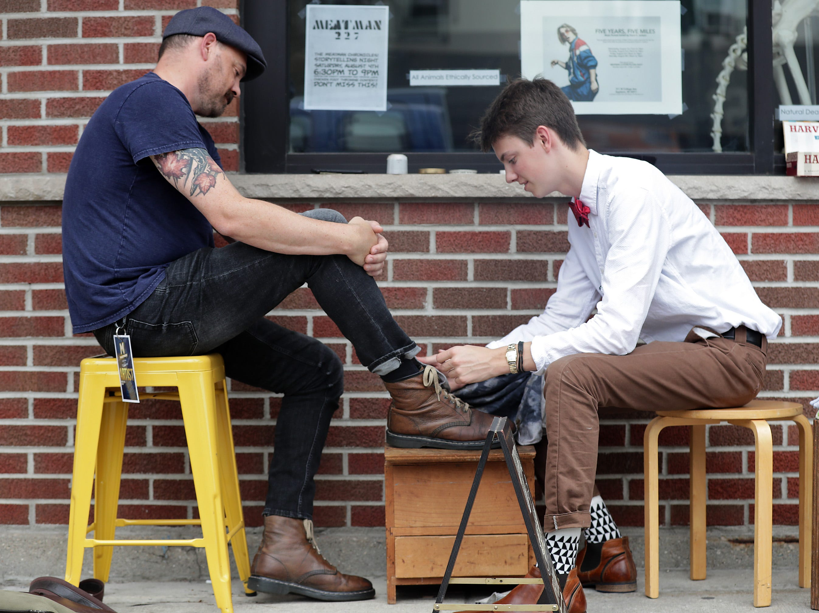 Kurt Gunn get his shoes shined by Henry Ptacdk during the Mile of Music festival Friday, August 3, 2018, in Appleton, Wis. 