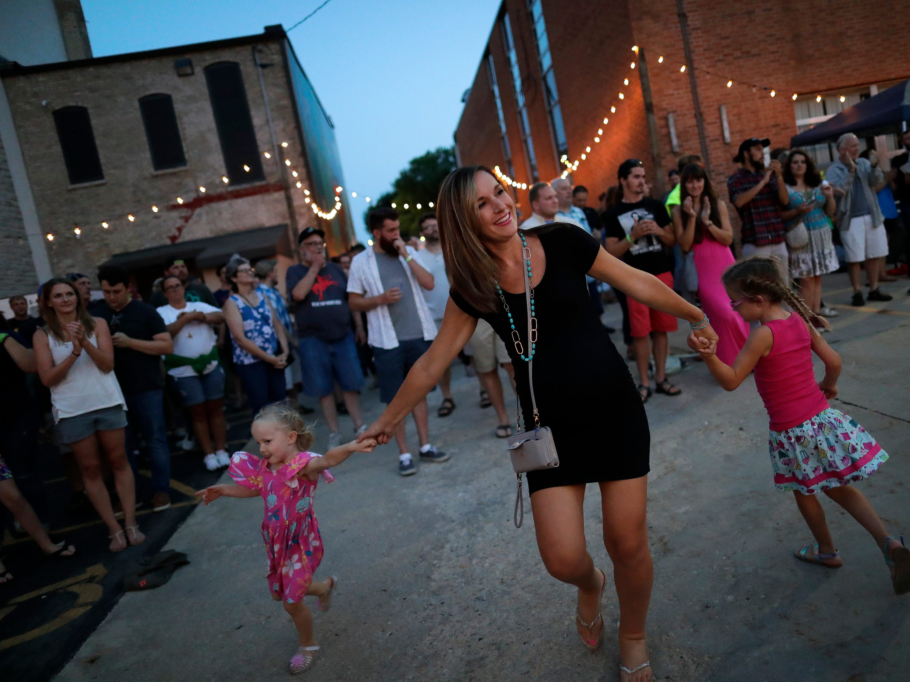 Jessica Strike of Menasha dances with her daughters Vivian, 4, left, and Melodi, 6, while listening to Good Night Gold Dust perform at the Alley Project during the Mile of Music Friday, August 3, 2018, in Appleton, Wis.  