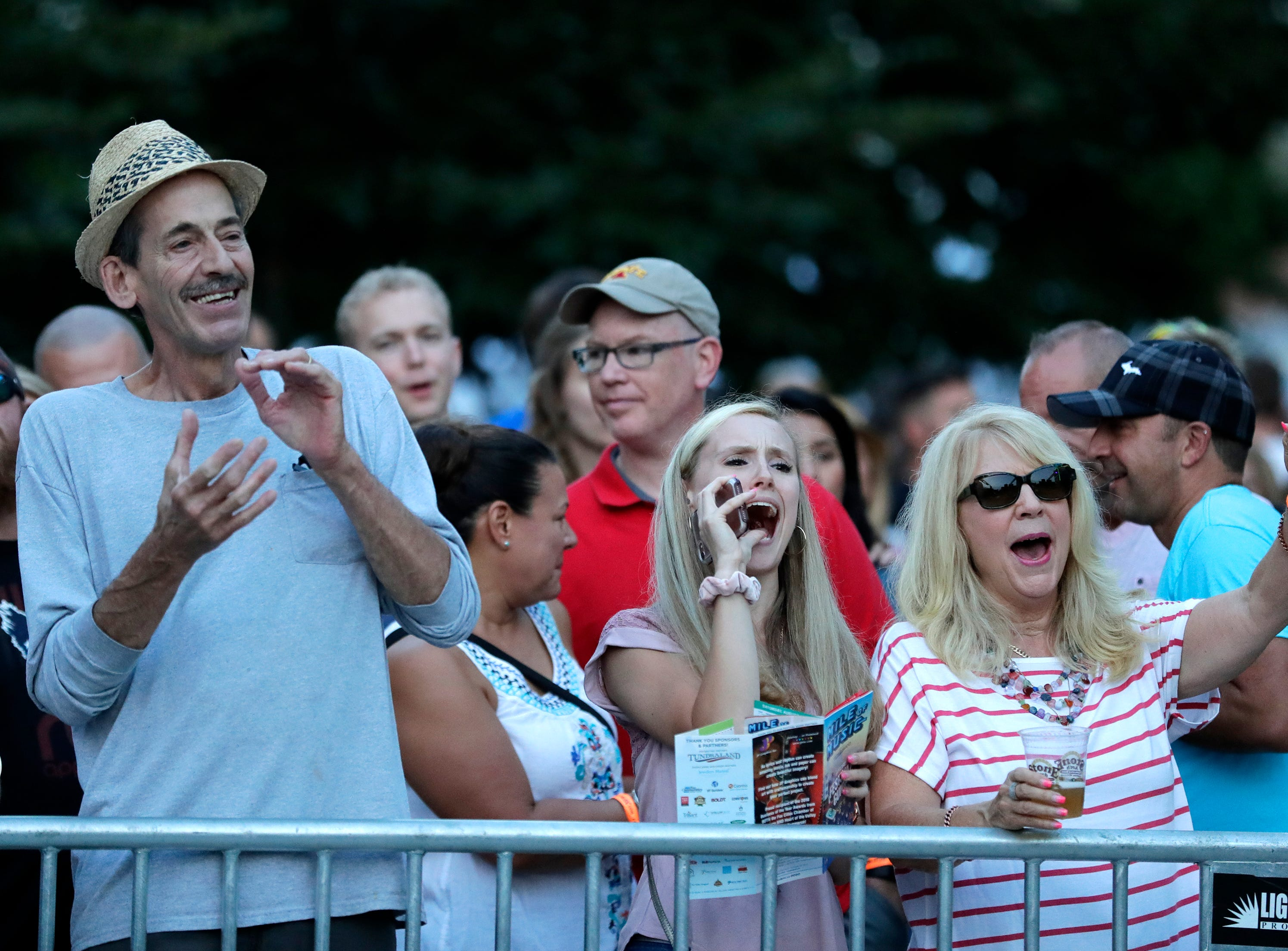 Fans cheer for The JC Brooks Band performance at Houdini Plaza during the Mile of Music Friday, August 3, 2018, in Appleton, Wis.  