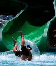 A swimmer tips over going after coming down one of the slides at Adventure Cove on Saturday.