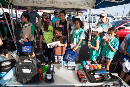 A group of Girl Scouts learn to check the air pressure and fill a tire during the Girl Scout Car Care Workshop on Saturday, Aug. 4, 2018.