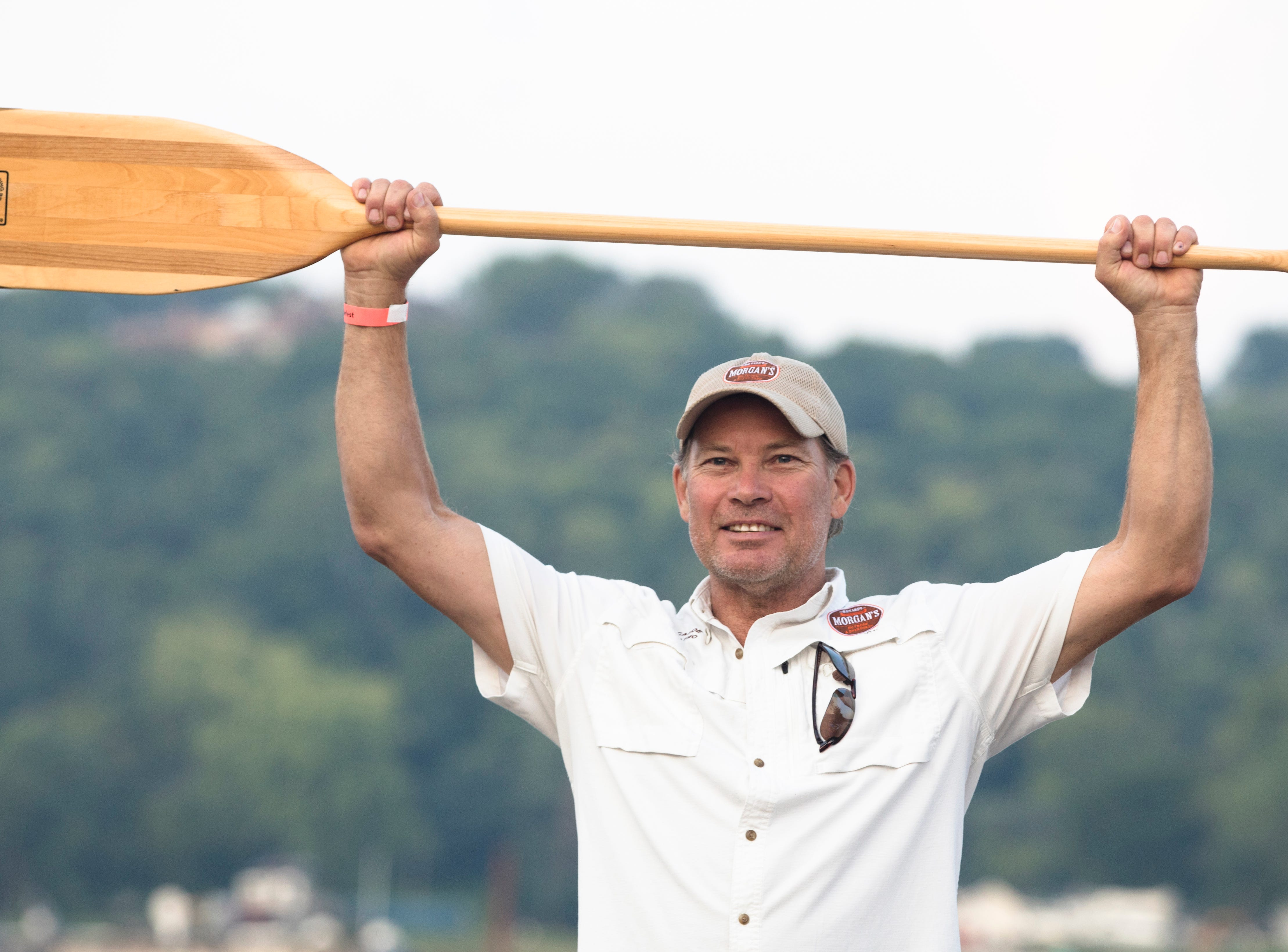 Dirk Morgan, son of Bob Morgan, holds up the ceremonial oar dedicated to his late father during the 17th annual Ohio River Paddlefest in Cincinnati on Saturday, Aug. 4, 2018.  According to organizers about 2000 people participated in the event which Outdoor Adventure Clubs of Greater Cincinnati raised almost $100,000.