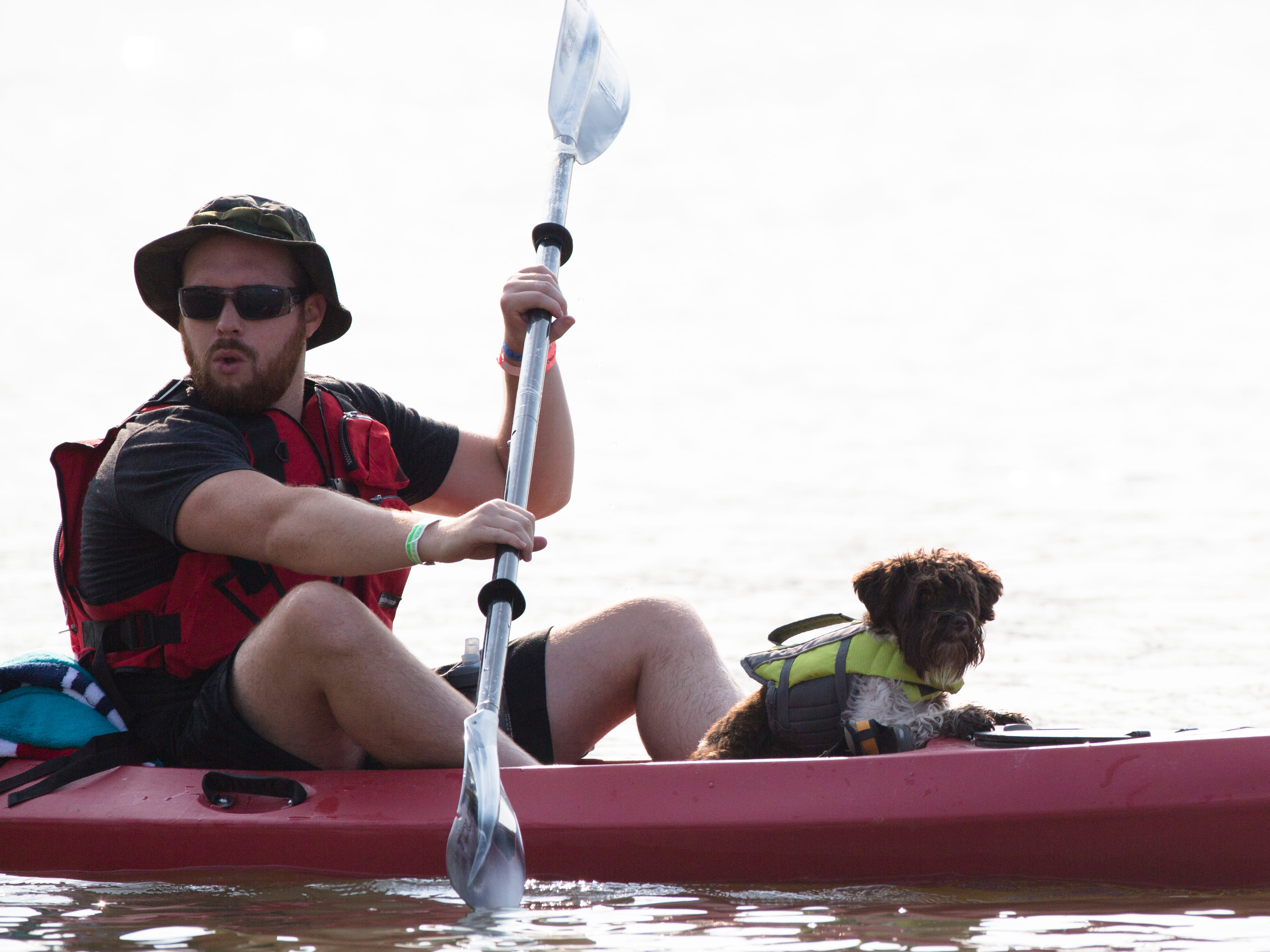 Will Gilliland paddles kayaks down the Ohio River with his dog, Cali, during the 17th annual Ohio River Paddlefest in Cincinnati on Saturday, Aug. 4, 2018.  According to organizers about 2000 people participated in the event which Outdoor Adventure Clubs of Greater Cincinnati raised almost $100,000.