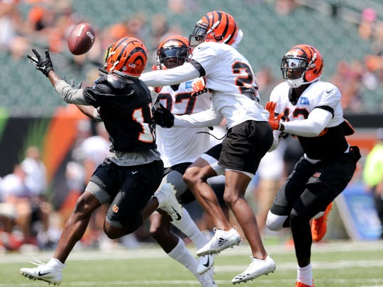 Cincinnati Bengals wide receiver Kermit Whitfield (17) catches a deep pass as Cincinnati Bengals cornerback William Jackson (22) Cincinnati Bengals defensive back Dre Kirkpatrick (27) and Cincinnati Bengals defensive back George Iloka (43) defend during Cincinnati Bengals training camp practice, Saturday, Aug. 4, 2018, at Paul Brown Stadium in Cincinnati.