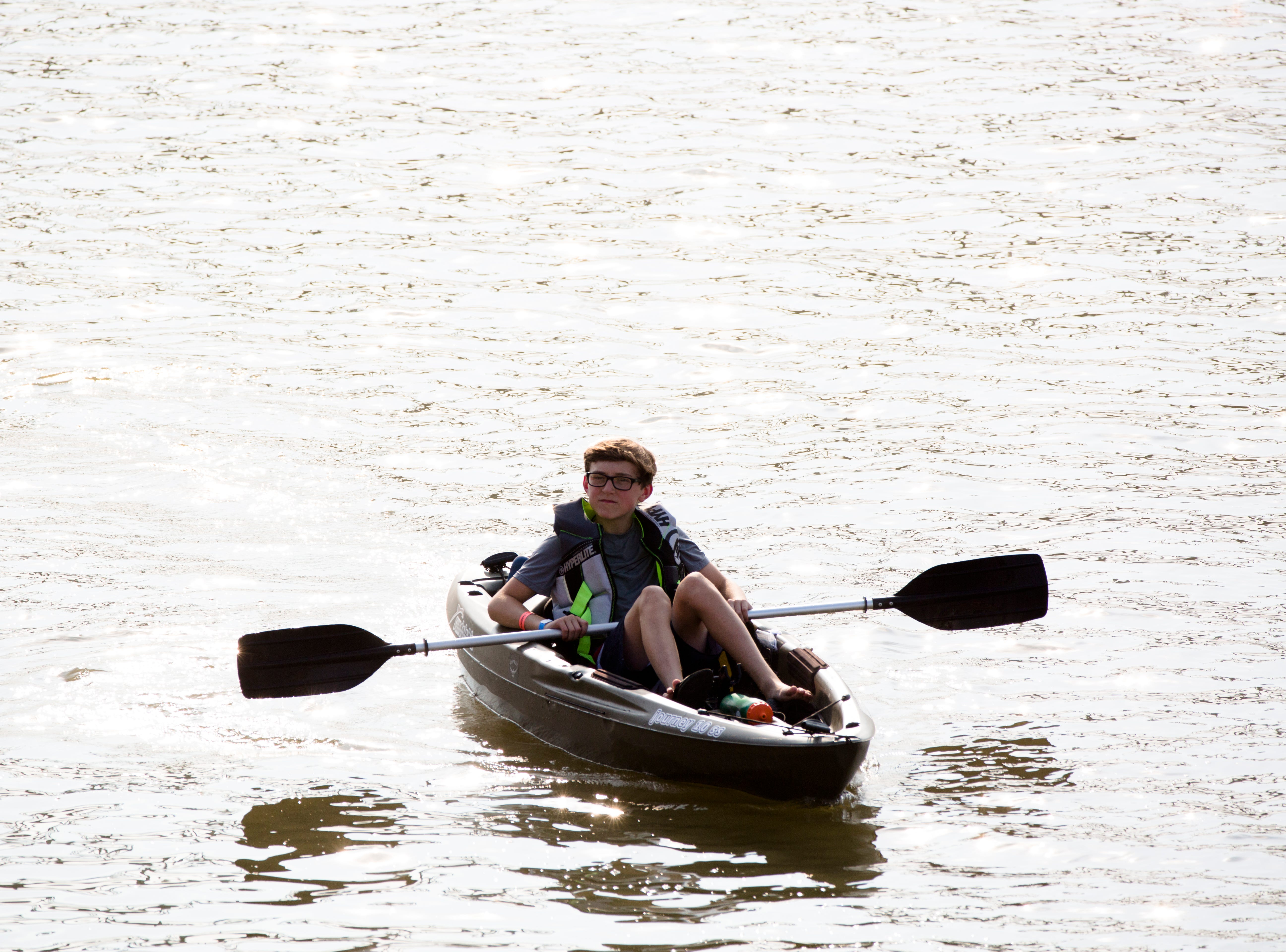 A person kayaks down the Ohio River during the 17th annual Ohio River Paddlefest in Cincinnati on Saturday, Aug. 4, 2018.  According to organizers about 2000 people participated in the event which Outdoor Adventure Clubs of Greater Cincinnati raised almost $100,000.