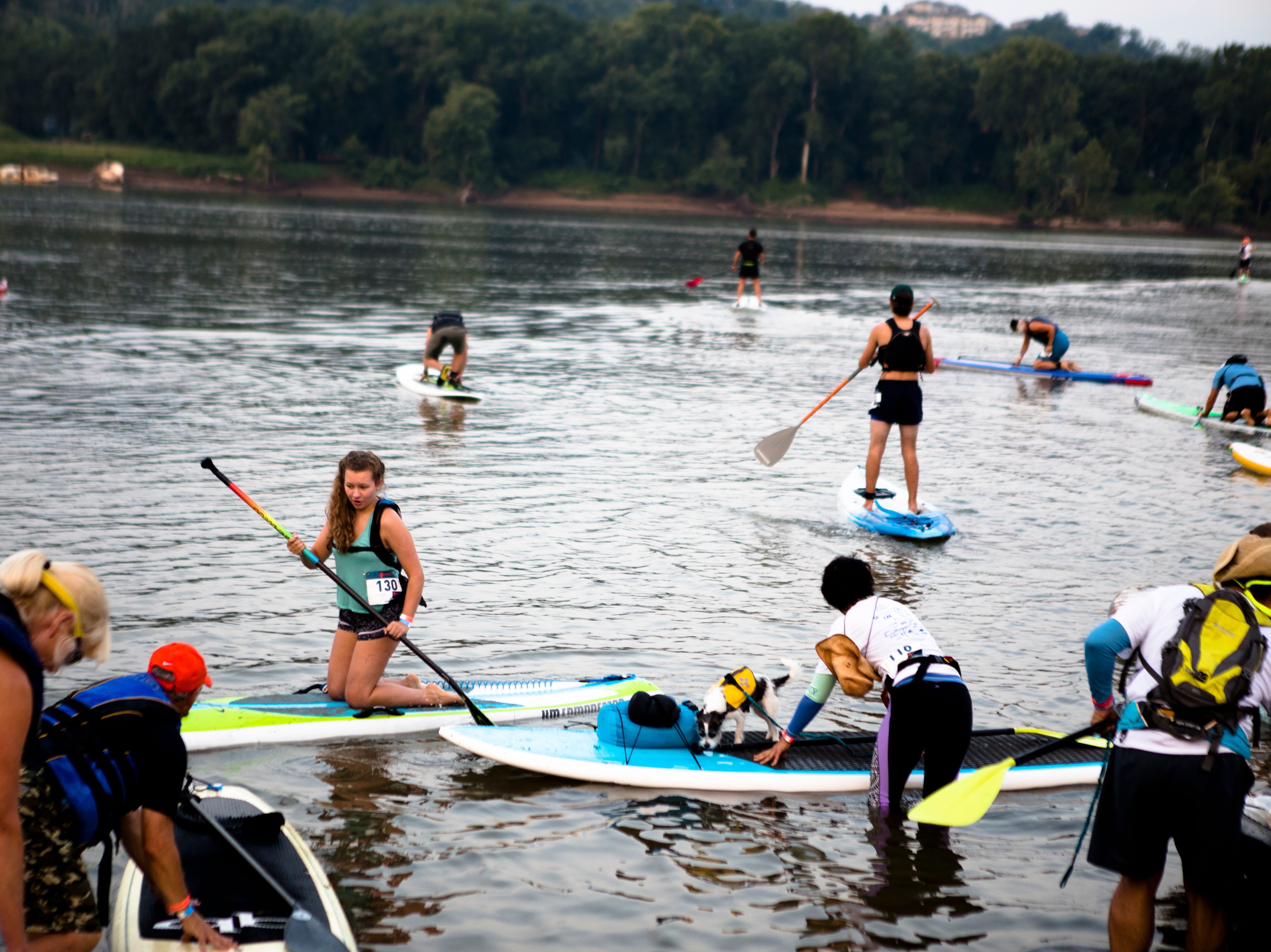 People paddle down the Ohio River on Canoes, Kayaks and Paddle Boards during the 17th annual Ohio River Paddlefest in Cincinnati on Saturday, Aug. 4, 2018.  According to organizers about 2000 people participated in the event which Outdoor Adventure Clubs of Greater Cincinnati raised almost $100,000.