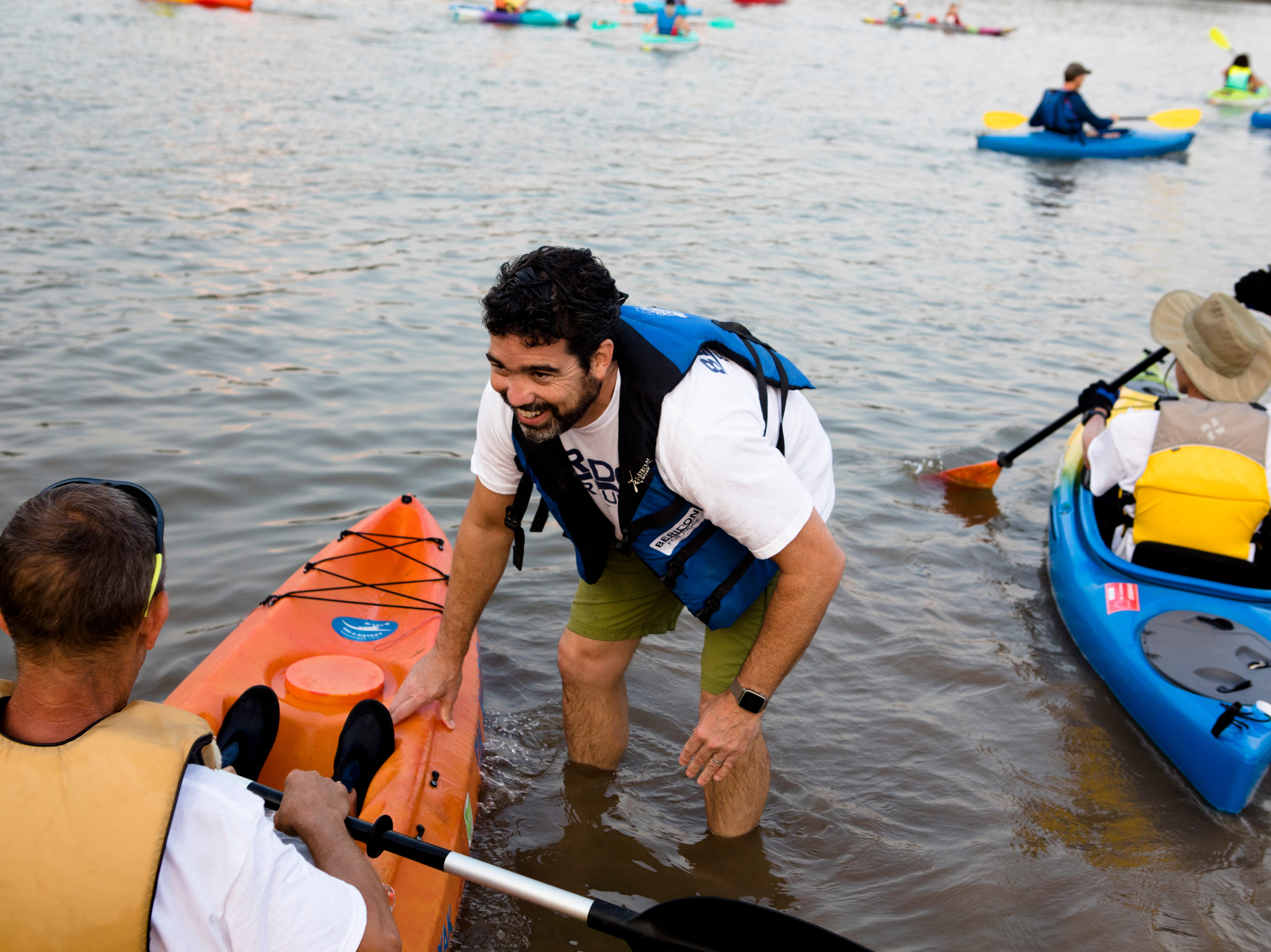 Tom Beridon helps people into the Ohio River during the 17th annual Ohio River Paddlefest in Cincinnati on Saturday, Aug. 4, 2018.  According to organizers about 2000 people participated in the event which Outdoor Adventure Clubs of Greater Cincinnati raised almost $100,000.