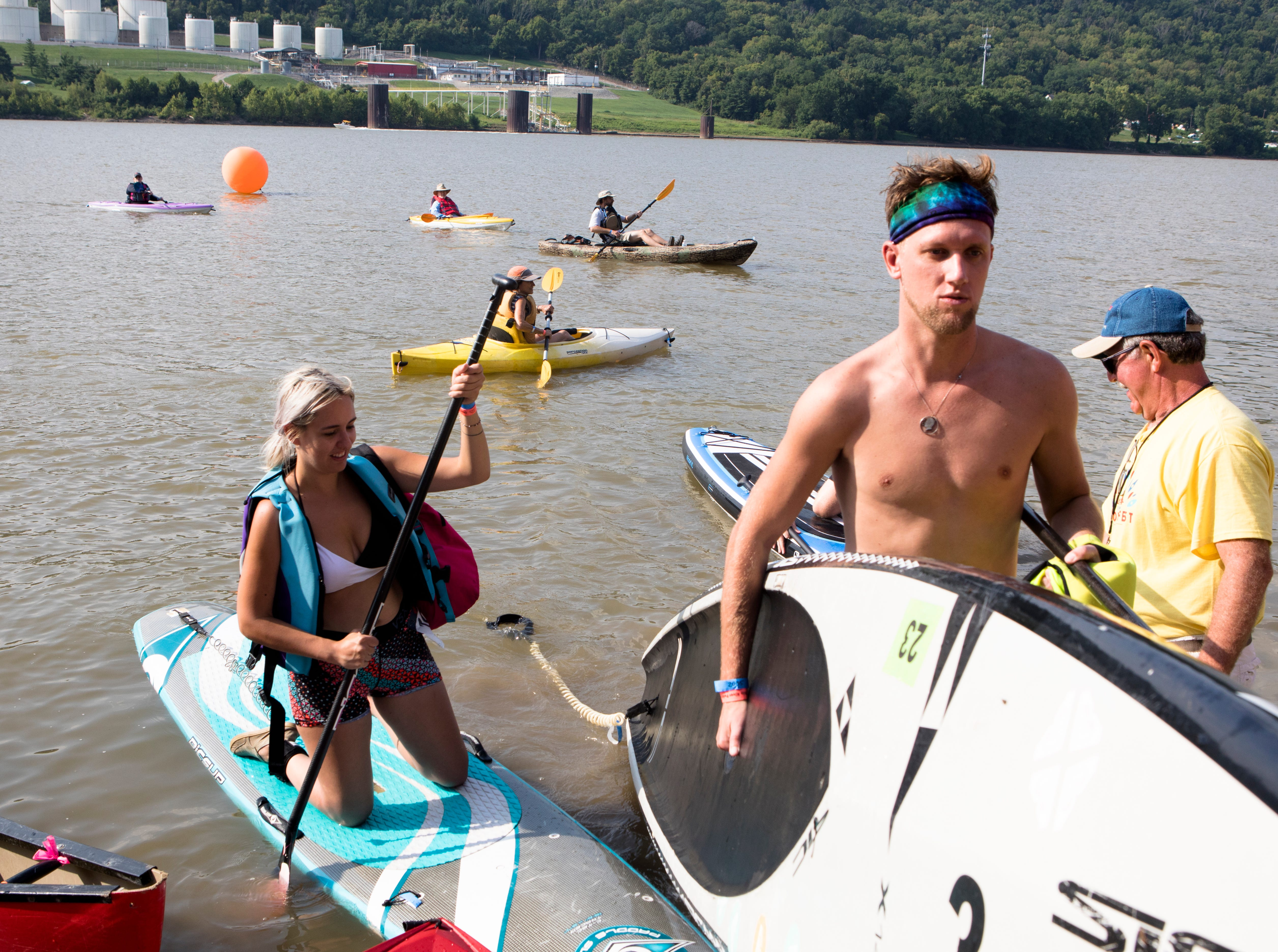 Andrew Hemmelgarn caries a paddle board after completing a 9 mile paddle board down the Ohio River during the 17th annual Ohio River Paddlefest in Cincinnati on Saturday, Aug. 4, 2018.  According to organizers about 2000 people participated in the event which Outdoor Adventure Clubs of Greater Cincinnati raised almost $100,000.
