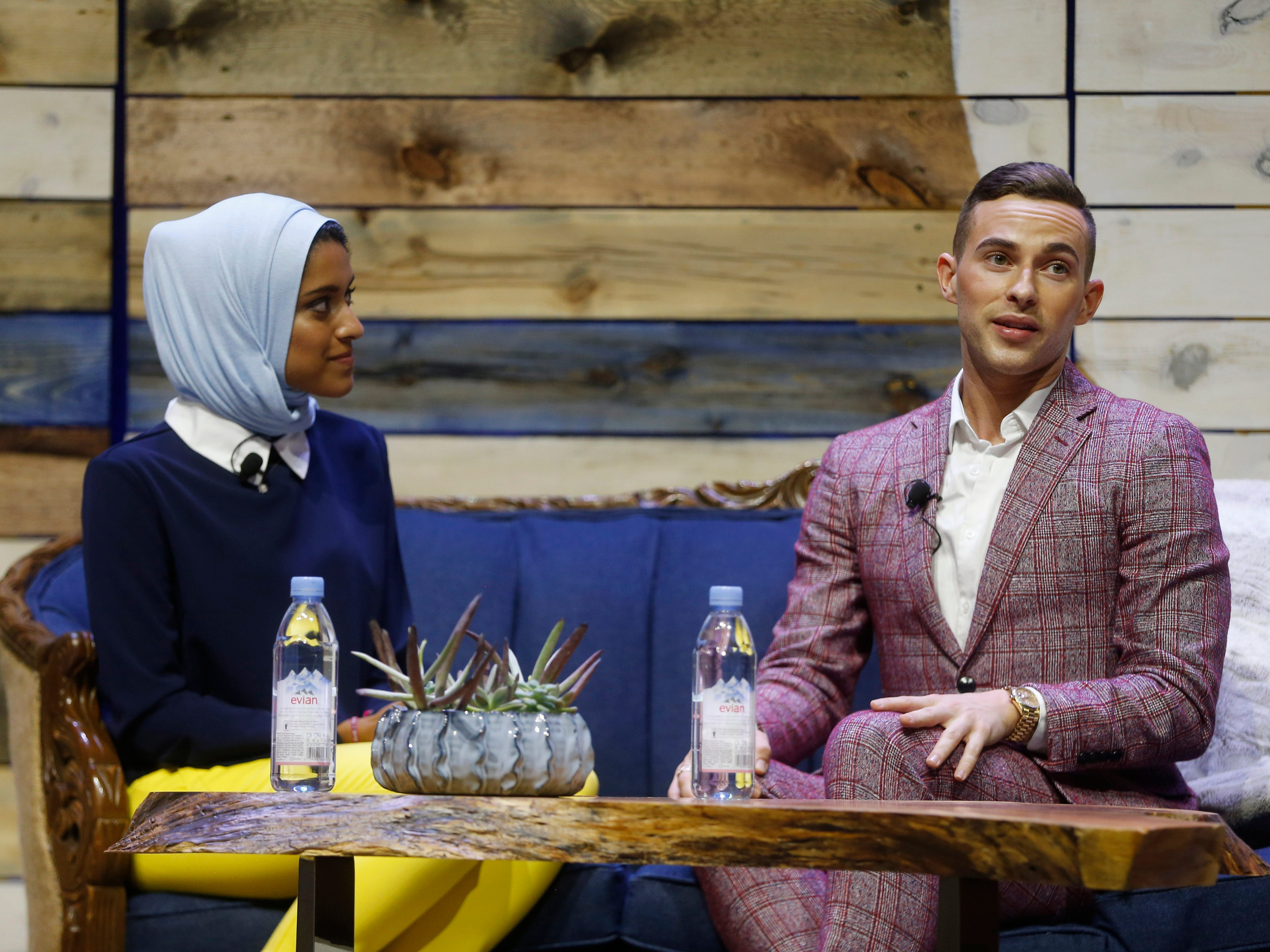Olympic figure skater Adam Rippon (right) talks with WHBF-TV reporter and moderator Tahera Rahman Saturday, Aug. 4, 2018, during a panel at Newbo Evolve, a three-day music, art and inspiration festival in Cedar Rapids, Iowa.