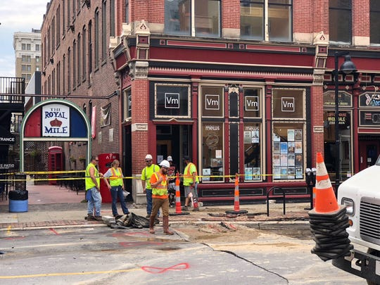 Cleanup begins on Fourth Avenue near the Royal Mile after water main breaks caused flooding following the Downtown Farmers' Market in Des Moines.