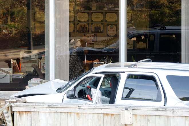 A woman continues to work inside Friday, Aug. 3, 2018, after an SUV fleeing  police crashed into the Des Moines Education Association building at 206 Center Street in downtown Des Moines.