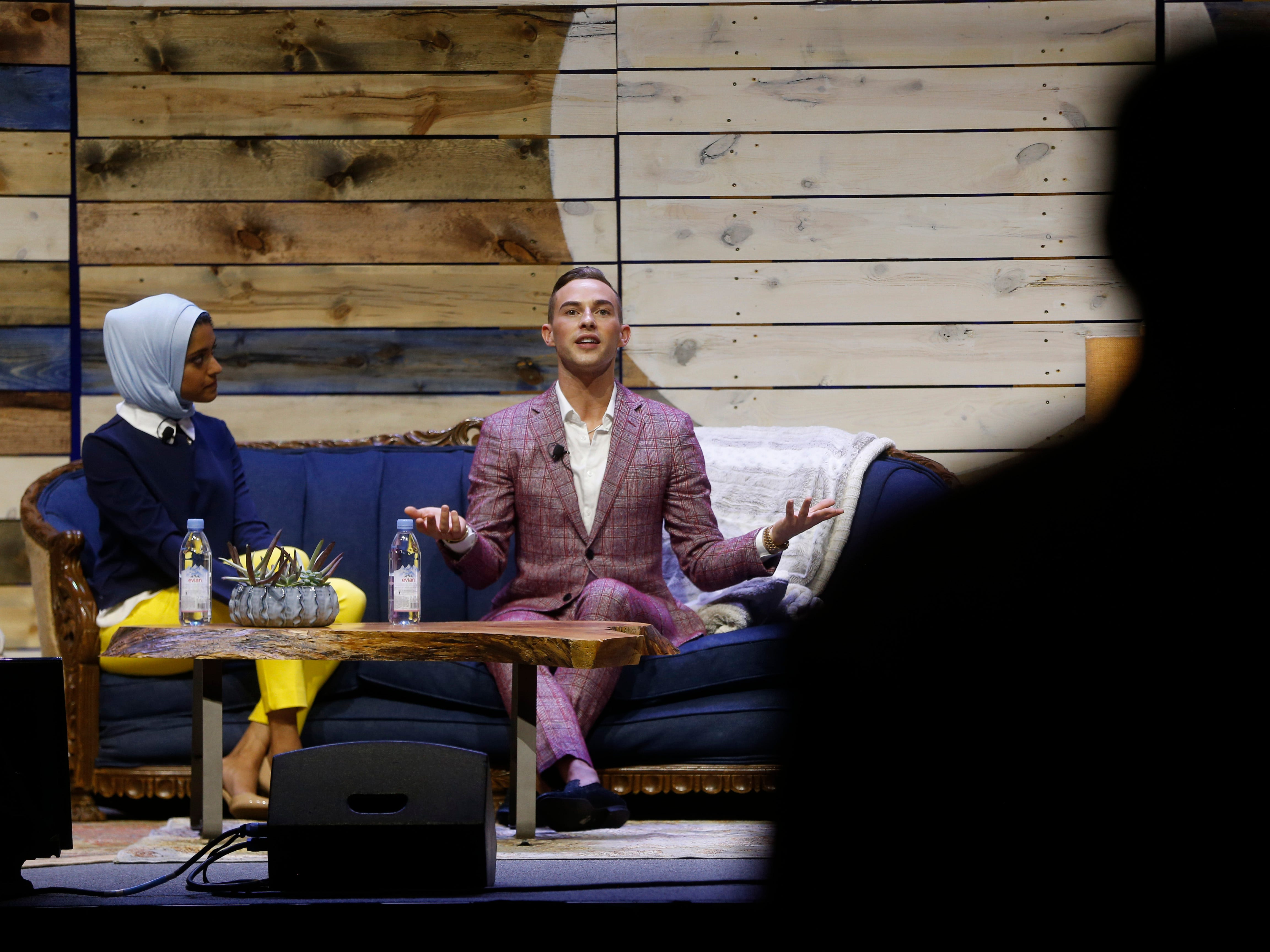 Olympic figure skater Adam Rippon (right) takes questions from the audience along side WHBF-TV reporter and moderator Tahera Rahman Saturday, Aug. 4, 2018, during a panel at Newbo Evolve, a three-day music, art and inspiration festival in Cedar Rapids, Iowa.