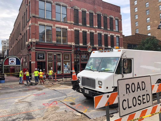 Cleanup begins on Fourth Avenue near Java Joe's after water main breaks caused flooding following the Downtown Farmers' Market in Des Moines.
