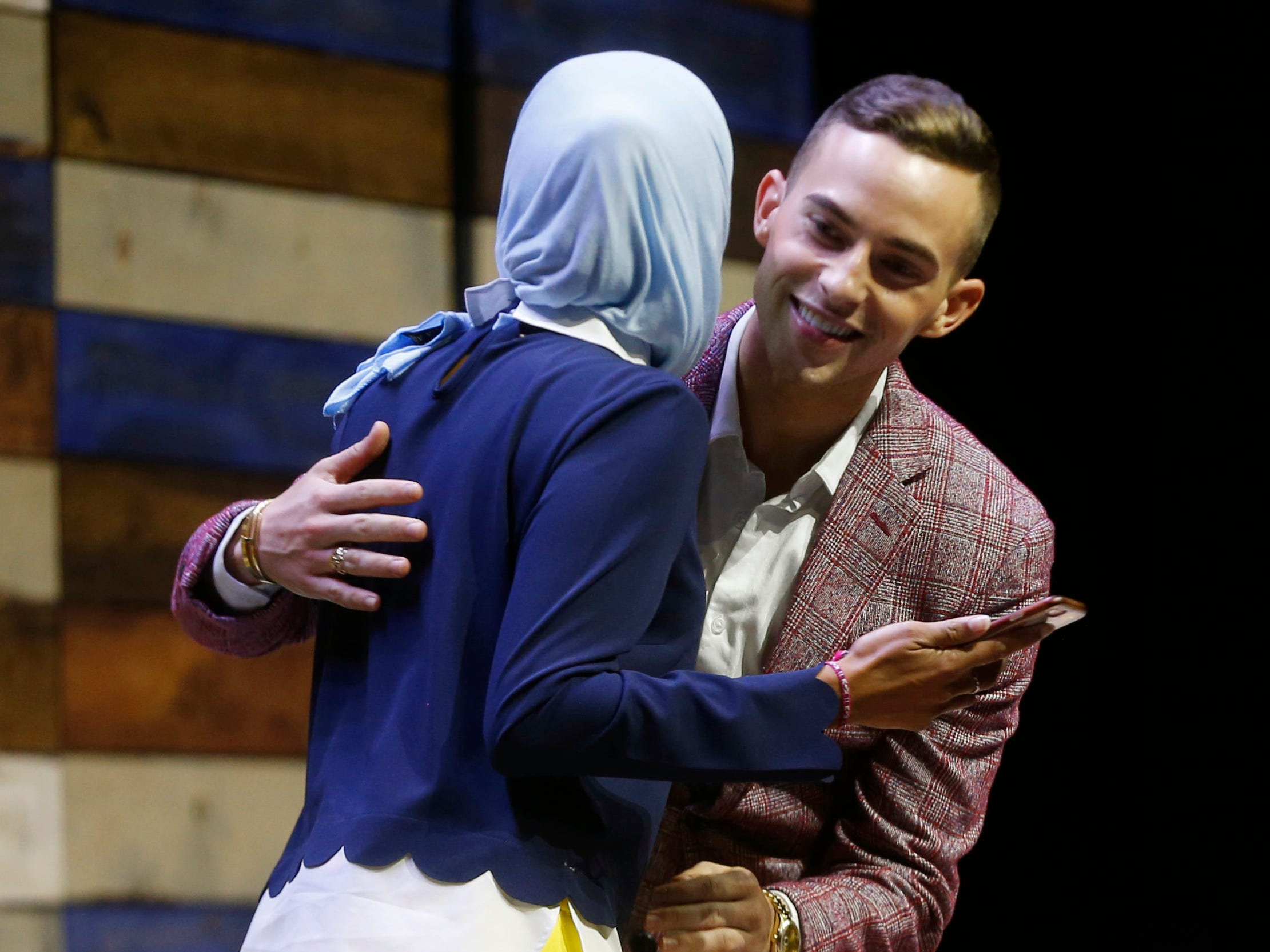 Olympic figure skater Adam Rippon (right) greets WHBF-TV reporter and moderator Tahera Rahman as he takes the stage Saturday, Aug. 4, 2018, at Newbo Evolve in Cedar Rapids, Iowa. The festival featured music, art and inspirational speakers over three days.