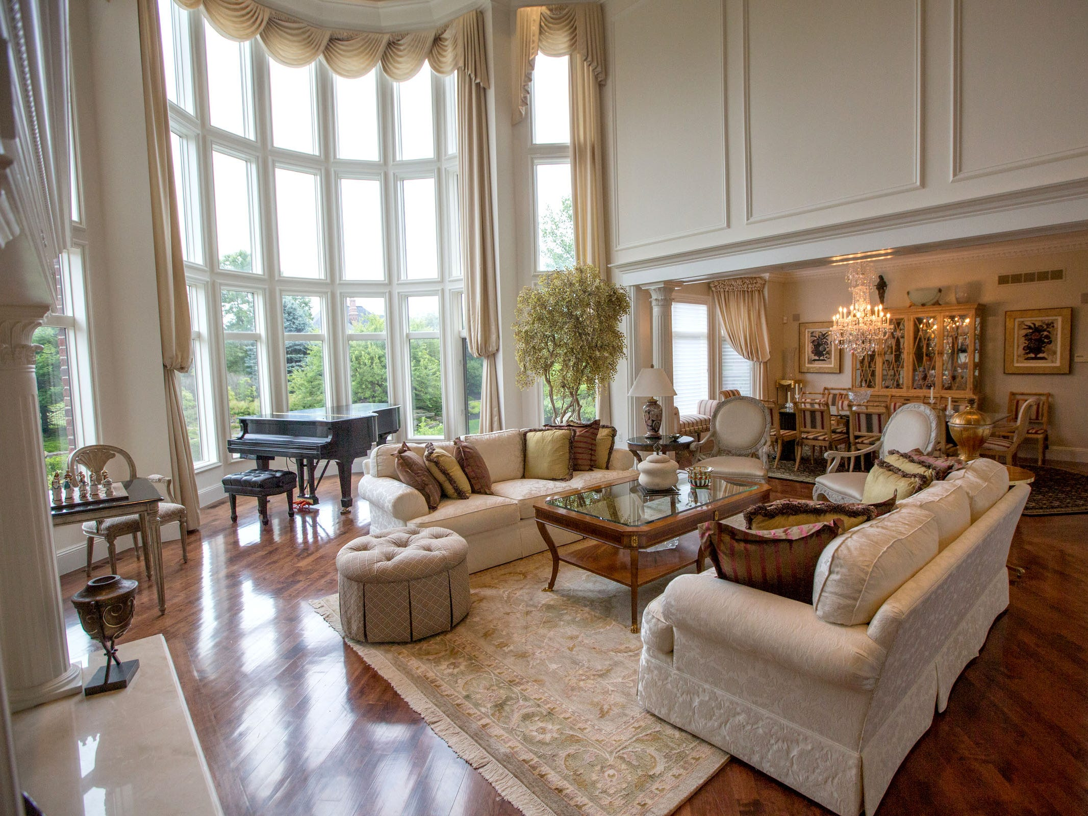 Windows are 30 feet high in the living room, with draperies that reach the floor. Pillars at the dining room entrance are a theme.