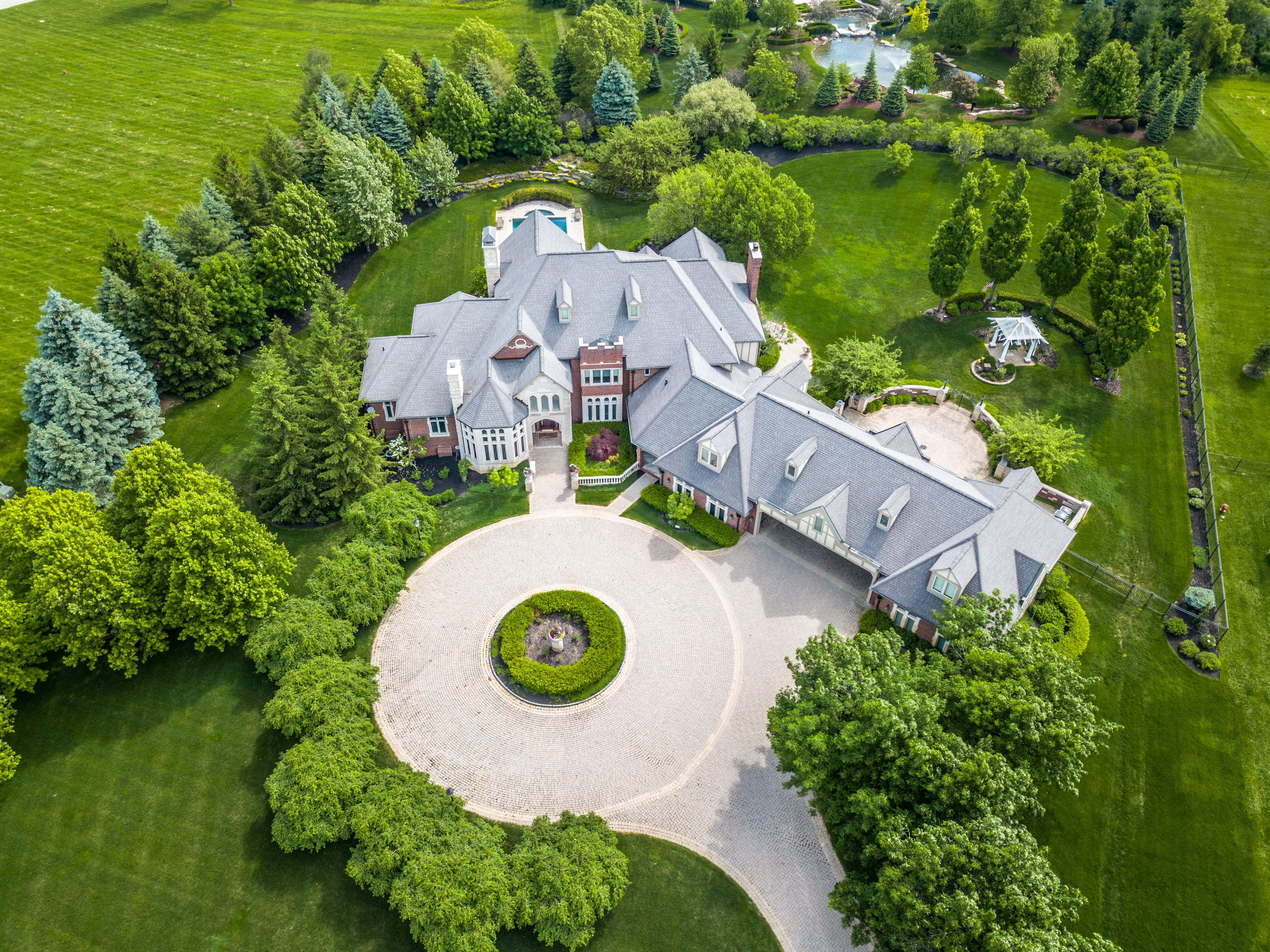 Key features: Opulent house in gated, guarded neighborhood, 2 great kitchens, great party space, great landscape and great garages for six cars.