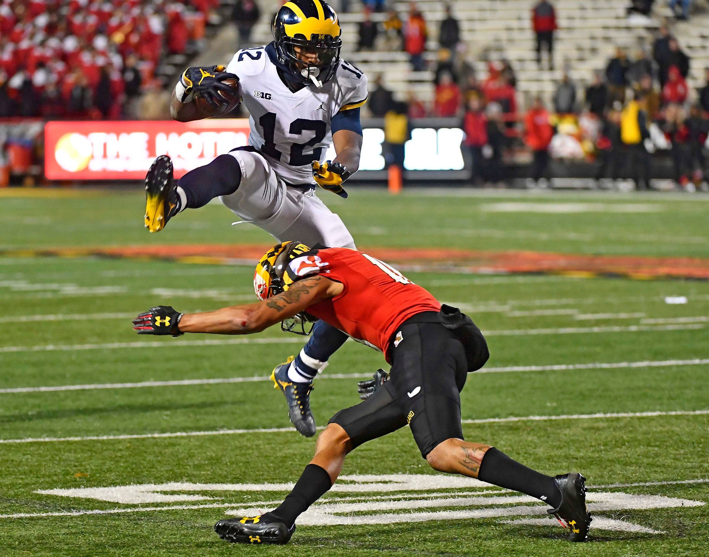 Michigan's Chris Evans leaps over a Maryland defender in 2017.