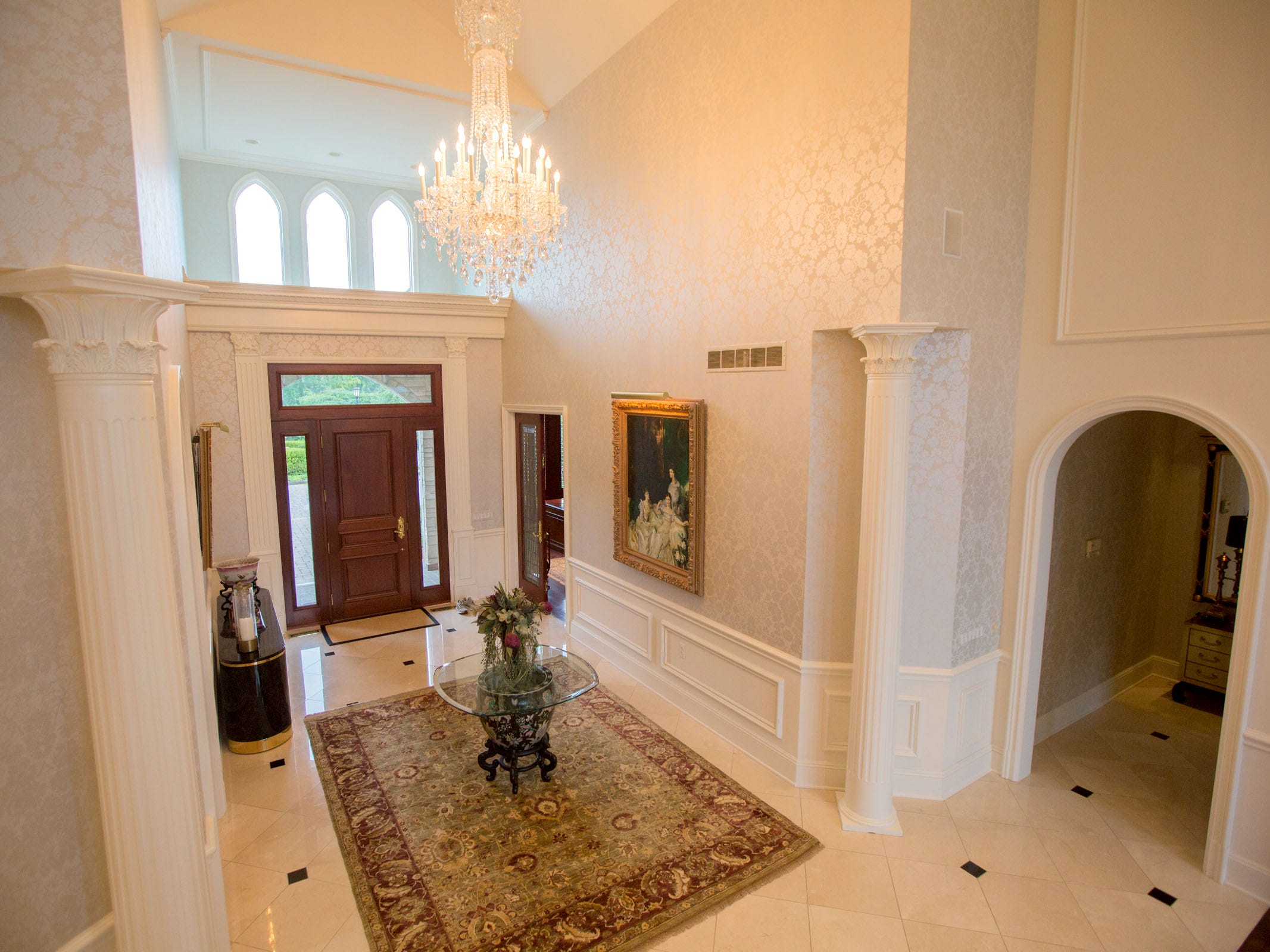 The tall entry hall continues the theme of white pillars and white marble.