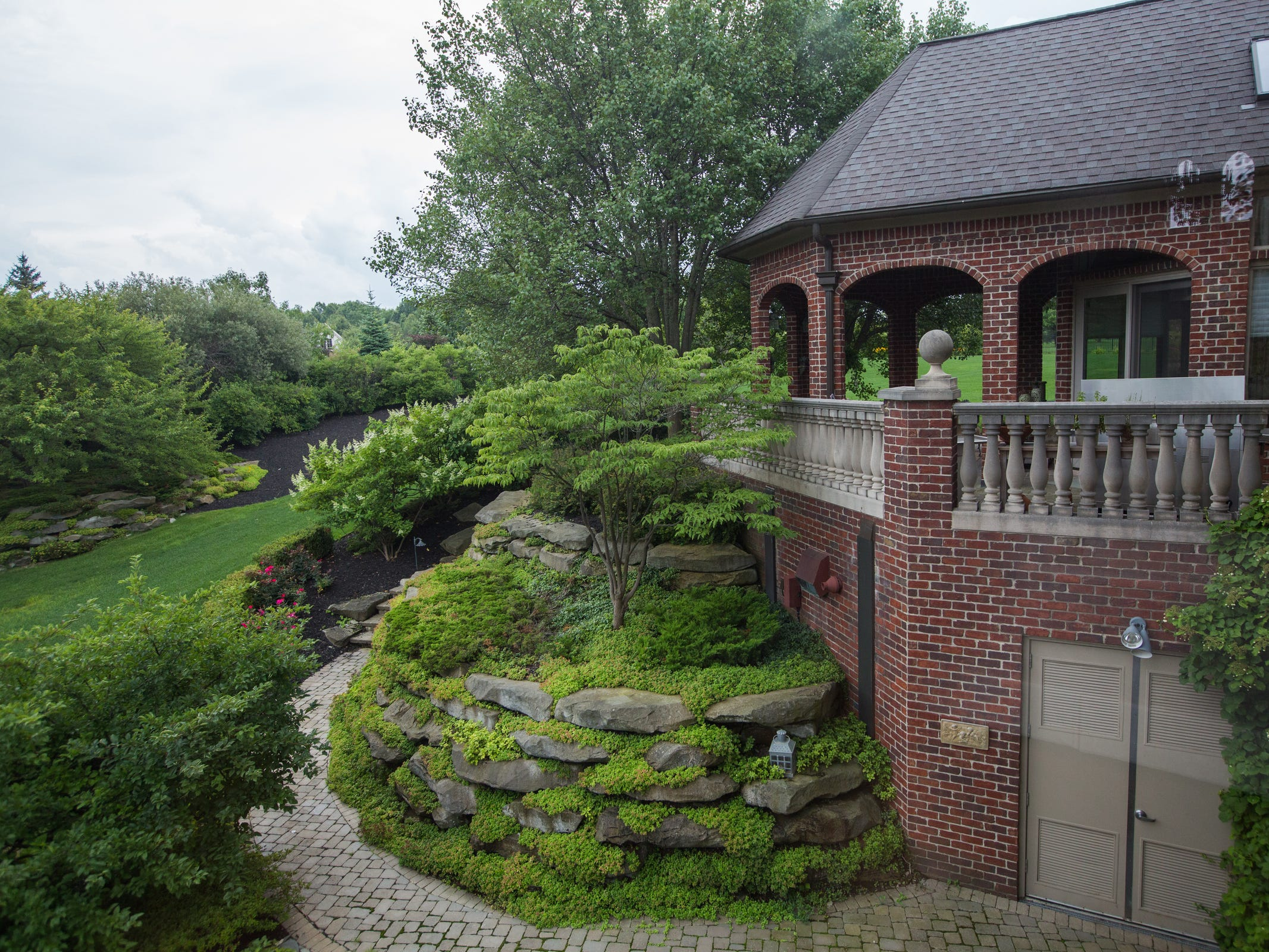 The landscaping is professional with all brick and stone, walls, stairs, an iron fence, a stream, a pond, dozens of conifers for privacy.