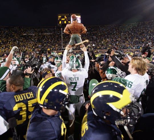 Michigan State QB Brian Hoyer raises the Paul Bunyan trophy, as Michigan players leave the field after Michigan State's 35-21 win in Ann Arbor on Oct. 25, 2008.