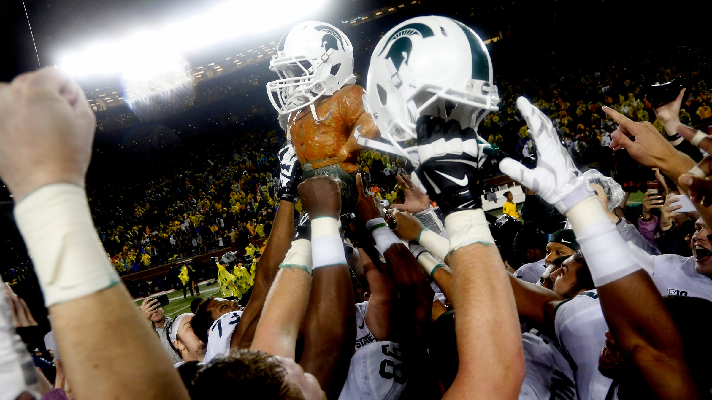 Michigan State players celebrate by raising the...