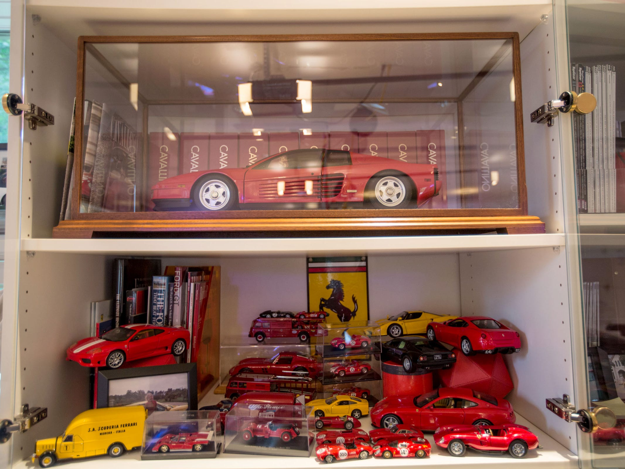 Part of the model car collection on display in a garage.