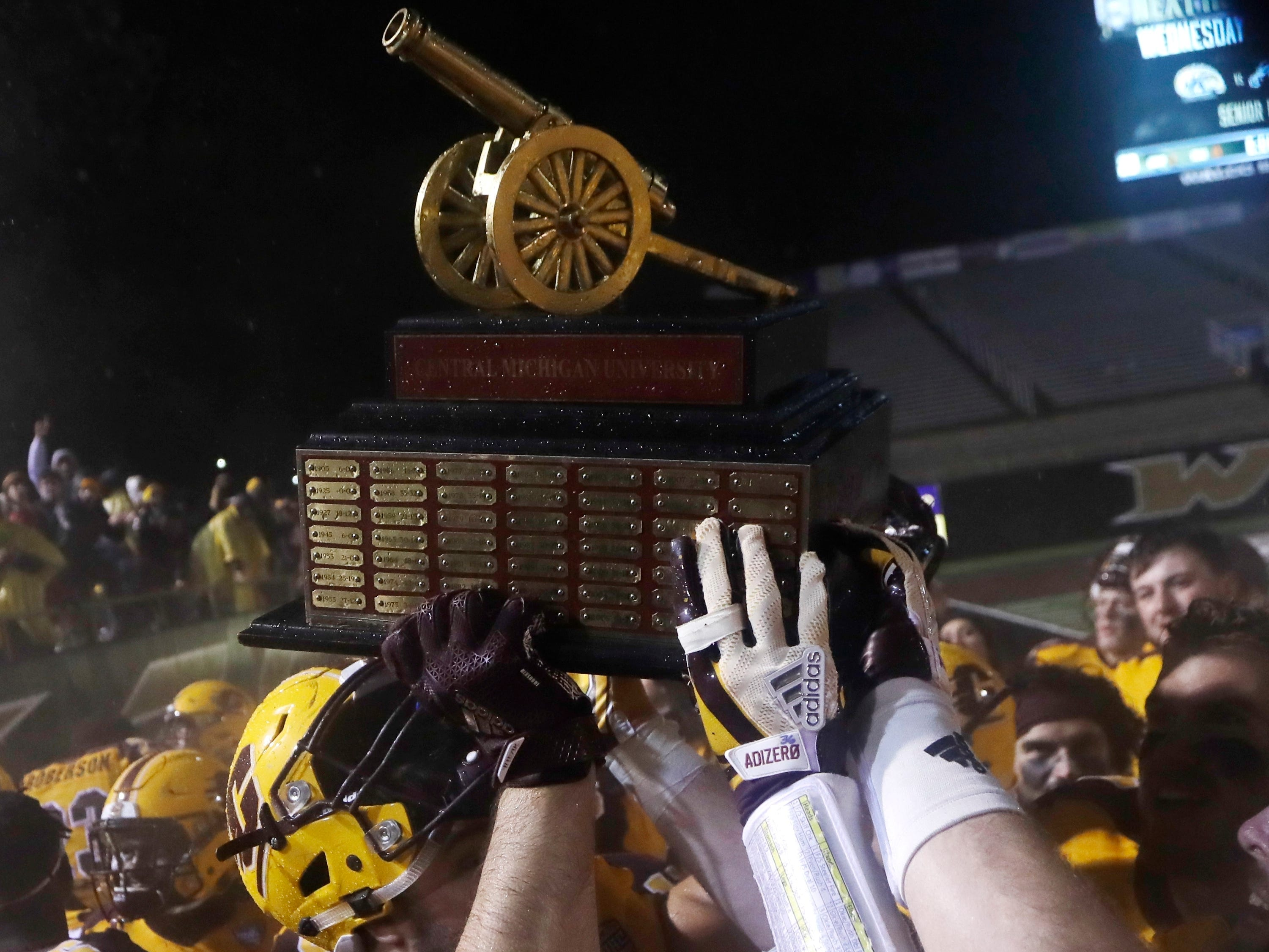 Central Michigan players hold the Victory Cannon trophy after their win against Western Michigan, Nov. 1, 2017, in Kalamazoo. The Victory Cannon is awarded to the winner of the in-state rivalry.