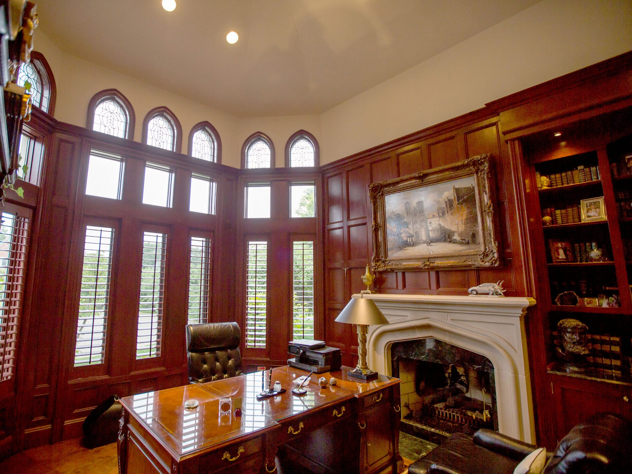 The library is lined with quarter-sawn mahogany paneling around a stone fireplace.