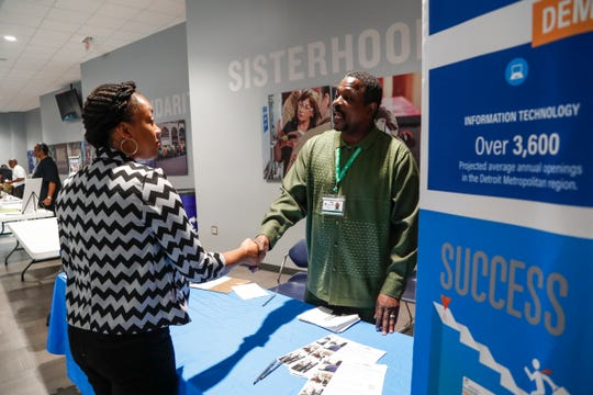 Focus Hope apprenticeship manager Kevin Green, right, talks Nikita Washington of Detroit during a joint UAW-IBEW sponsored job fair at the International Brotherhood of Electrical Workers Local 58 in Detroit, Saturday, August 4, 2018.