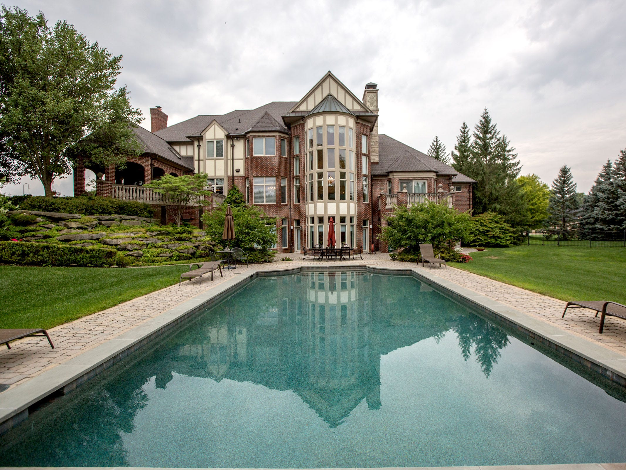 Belgian brick surrounds the pool. At the main level of the house, large brick terraces are ringed with stone balustrades.