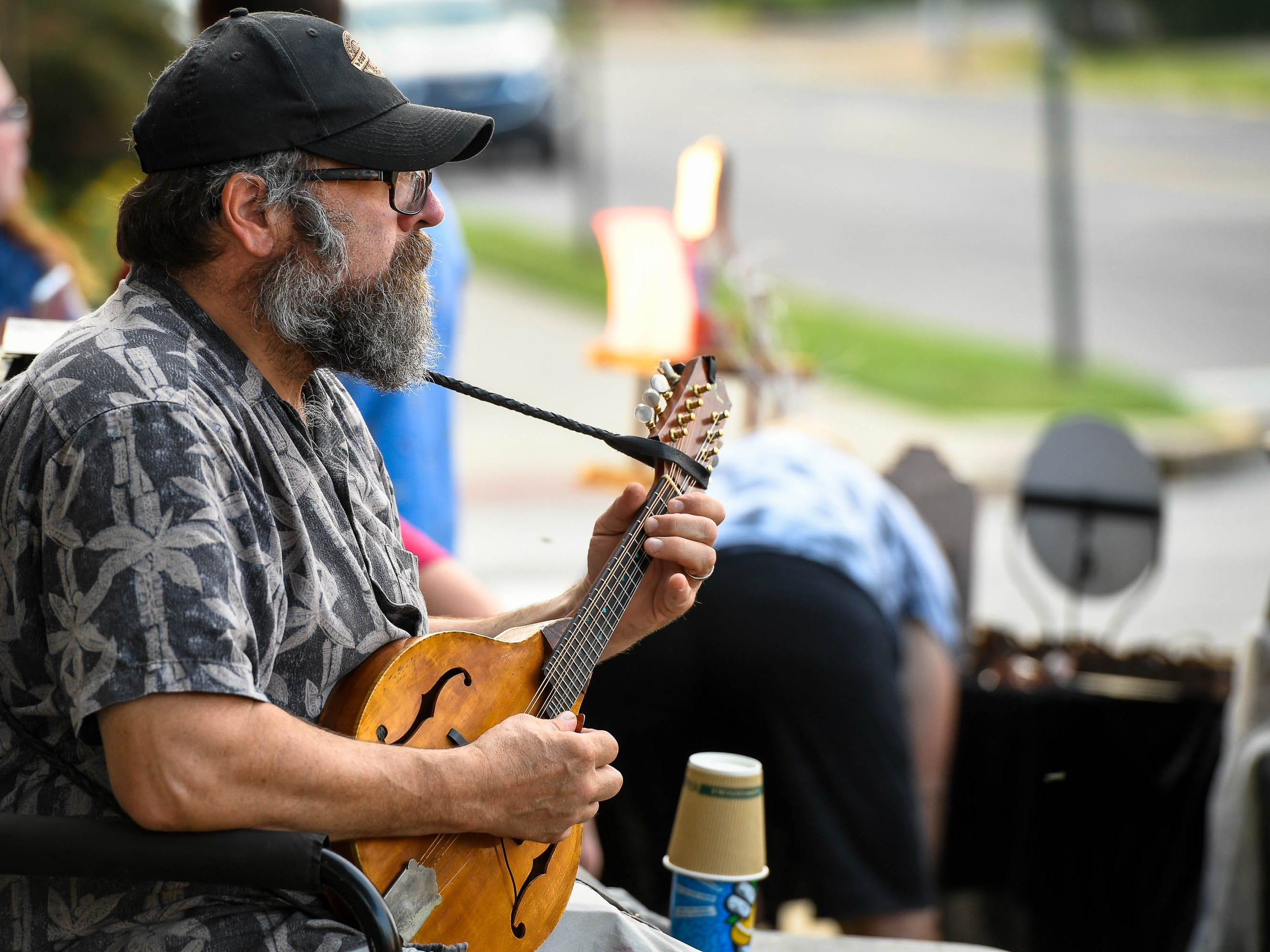 Tim Piazza plays the mandolin while tending his Evansville Coffee Company booth during the Haynie's Corner First Friday event in the downtown Arts District Friday, August 3, 2018.