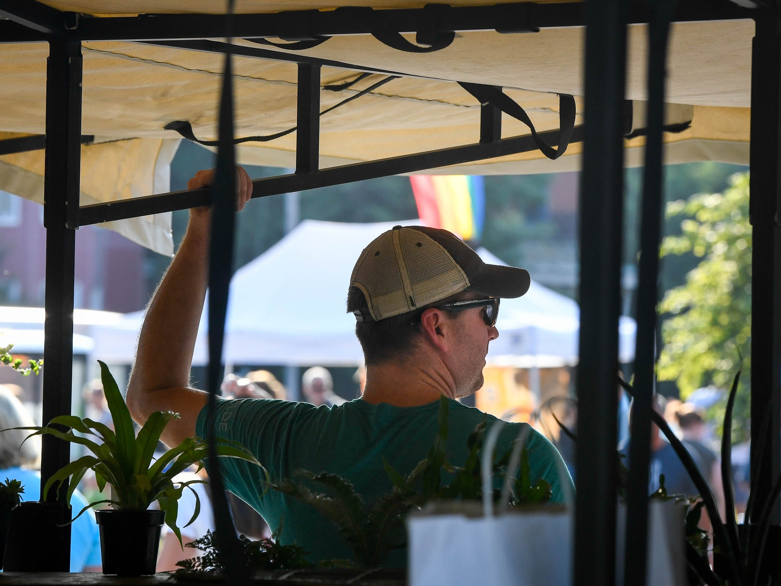 Looking out over the Arts District, Brian Wildeman tends to his truck selling horticultural items at the Haynie's Corner First Friday event in the downtown Evansville Friday, August 3, 2018.