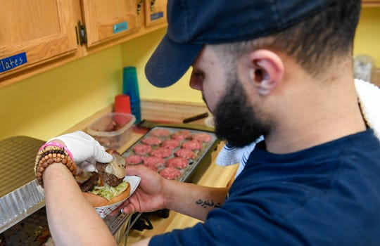 Stephan Sims assembles a couple double patty cheese sliders with Swiss and bacon served up by the Turn Table Mobile Cuisine at Patch Work Central during the Haynie's Corner First Friday event in the downtown Arts District Friday, August 3, 2018.