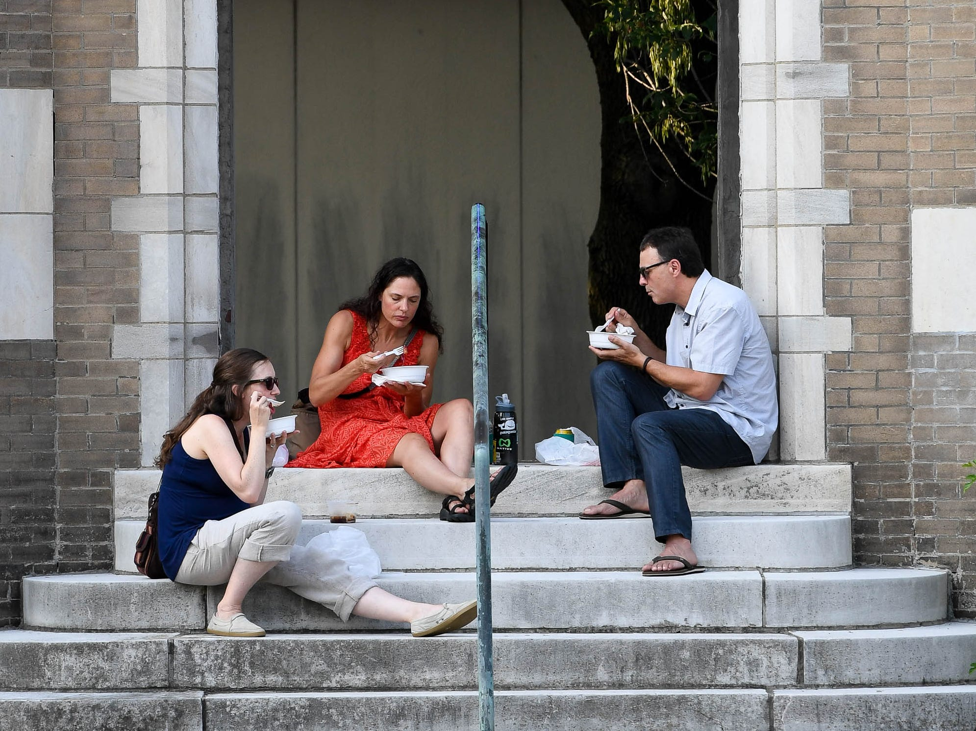 Enjoying their food truck dinners, left to right, Jennie Grafton, Amy Good and Dale Edwards set on the steps of the tower by Patch Work Central during the Haynie's Corner First Friday in the downtown Arts District Friday, August 3, 2018.