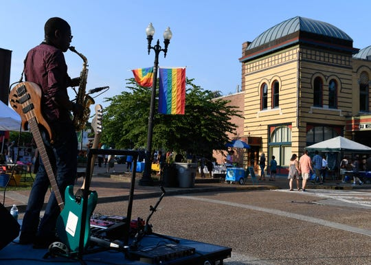 Monte Skelton fills the air at aynie's Corner with music as he plays his sax for the crow at the First Friday event in the downtown Arts District Friday, August 3, 2018.