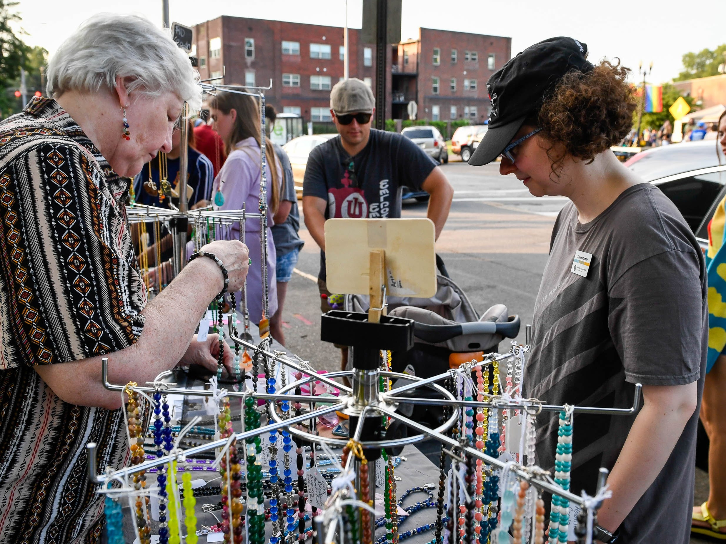 Karen Malone, right, buys a neckless from Marilla Walthen at her R&J Chakra Jewelry table during the Haynie's Corner First Friday event in the downtown Arts District Friday, August 3, 2018.