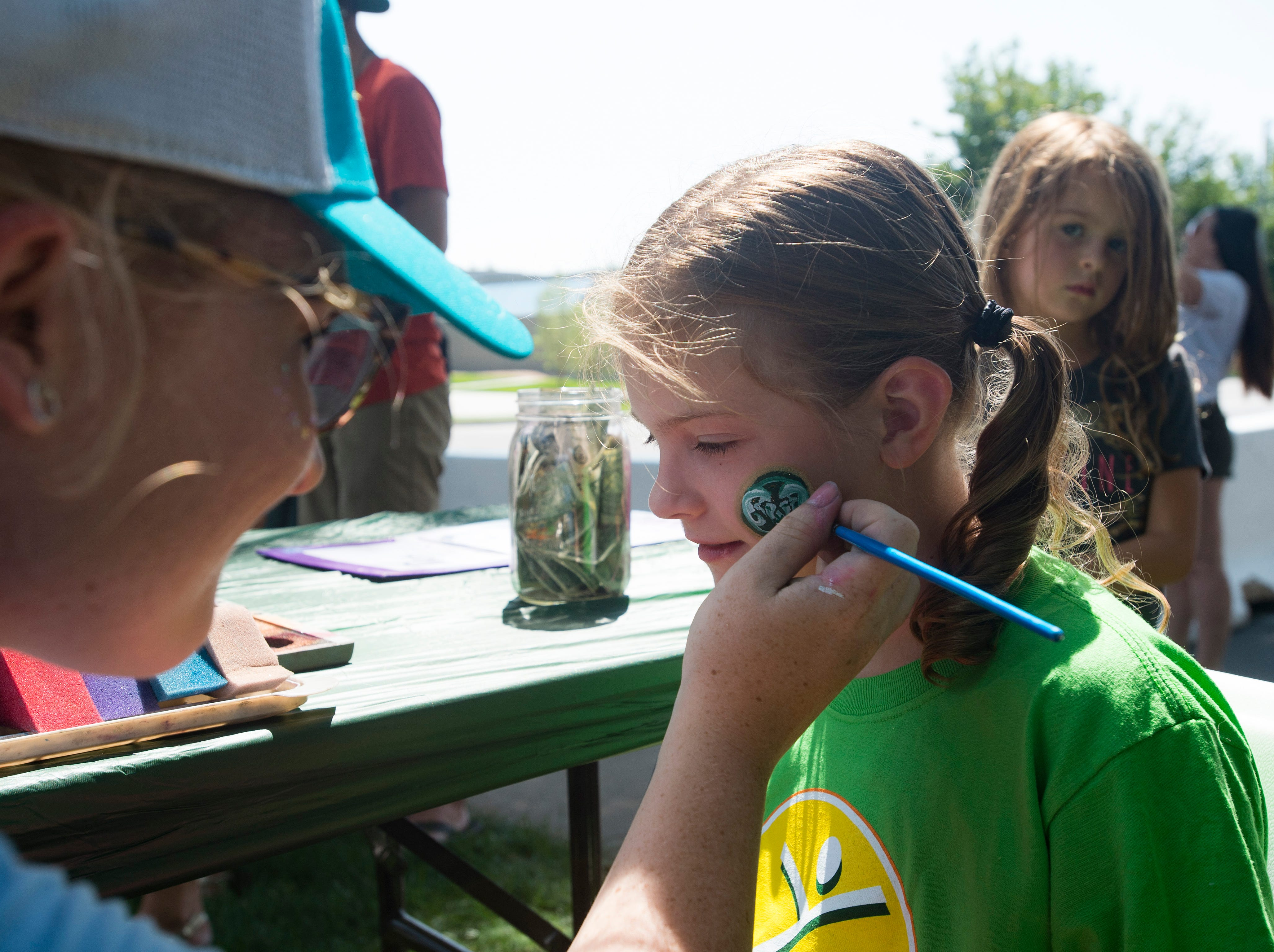 Madison Gasper, 7, shows her CSU spirit by having her face painted during an open house and scrimmage hosted by the Rams outside of Canvas Stadium on Saturday, August 4, 2018.