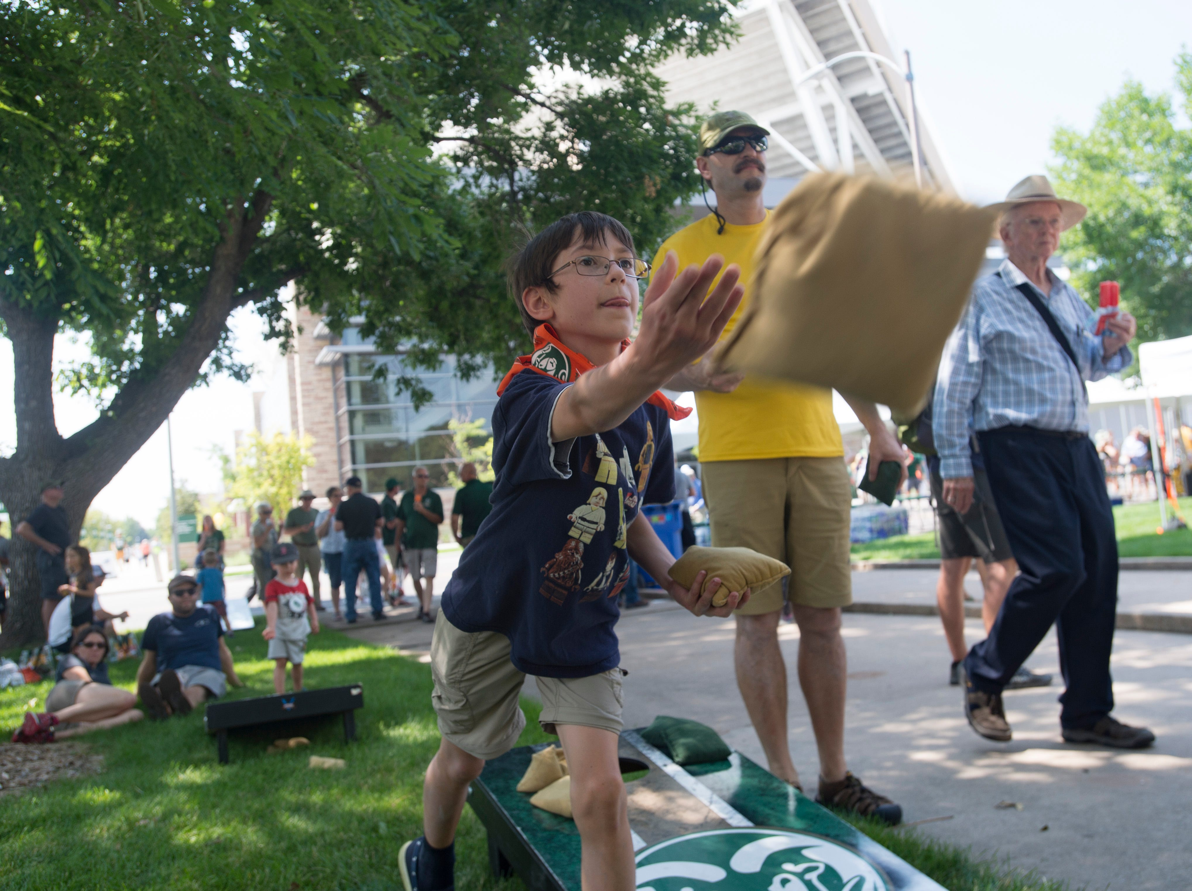 Rams fan Silas Malers, 11, plays a game of corn hole with his father, Steve, during an open house and scrimmage hosted by the Rams outside of Canvas Stadium on Saturday, August 4, 2018.
