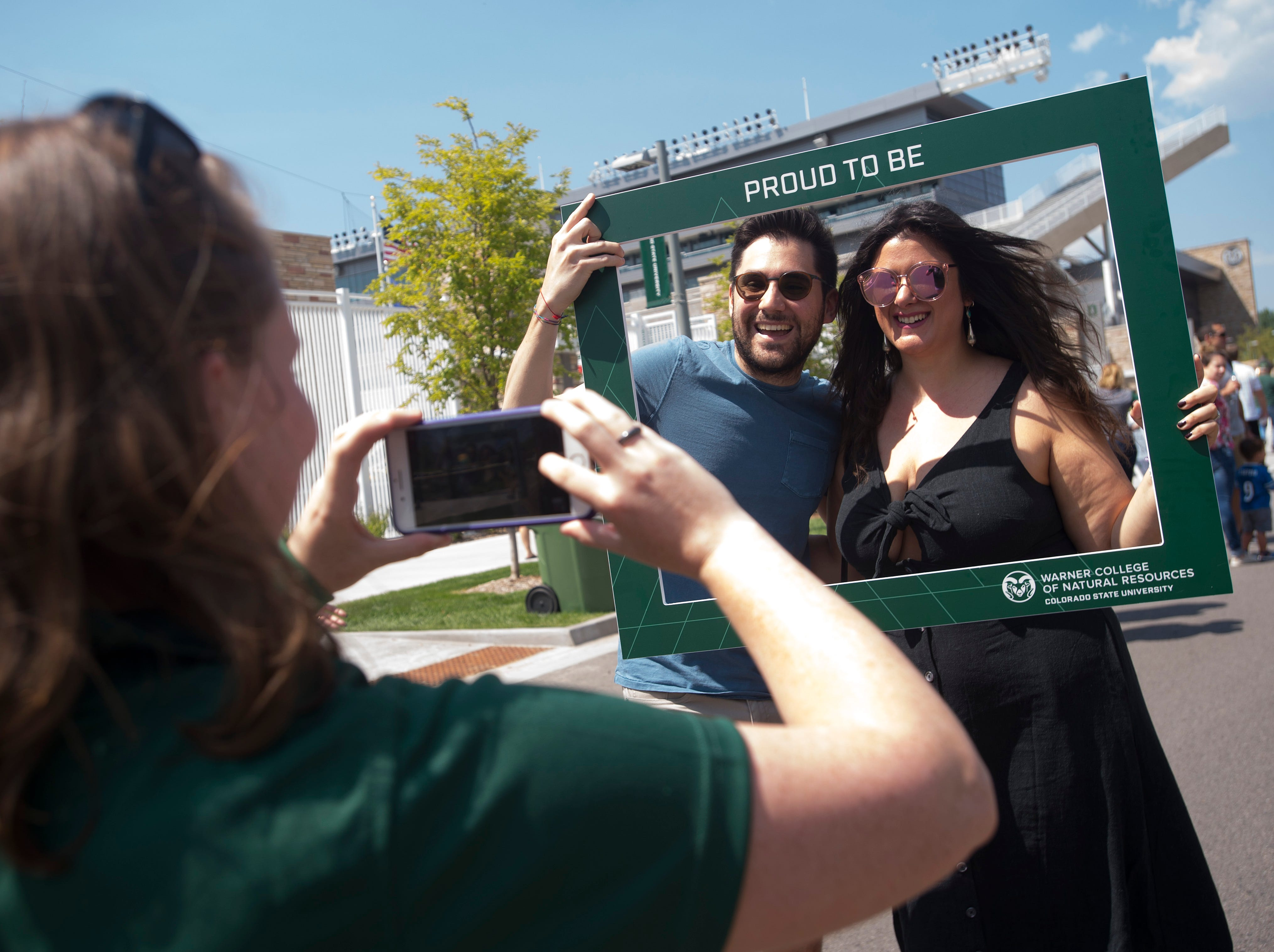 CSU fans Alberto and Patrice Basaglia take a photo during an open house and scrimmage hosted by the Rams outside of Canvas Stadium on Saturday, August 4, 2018.