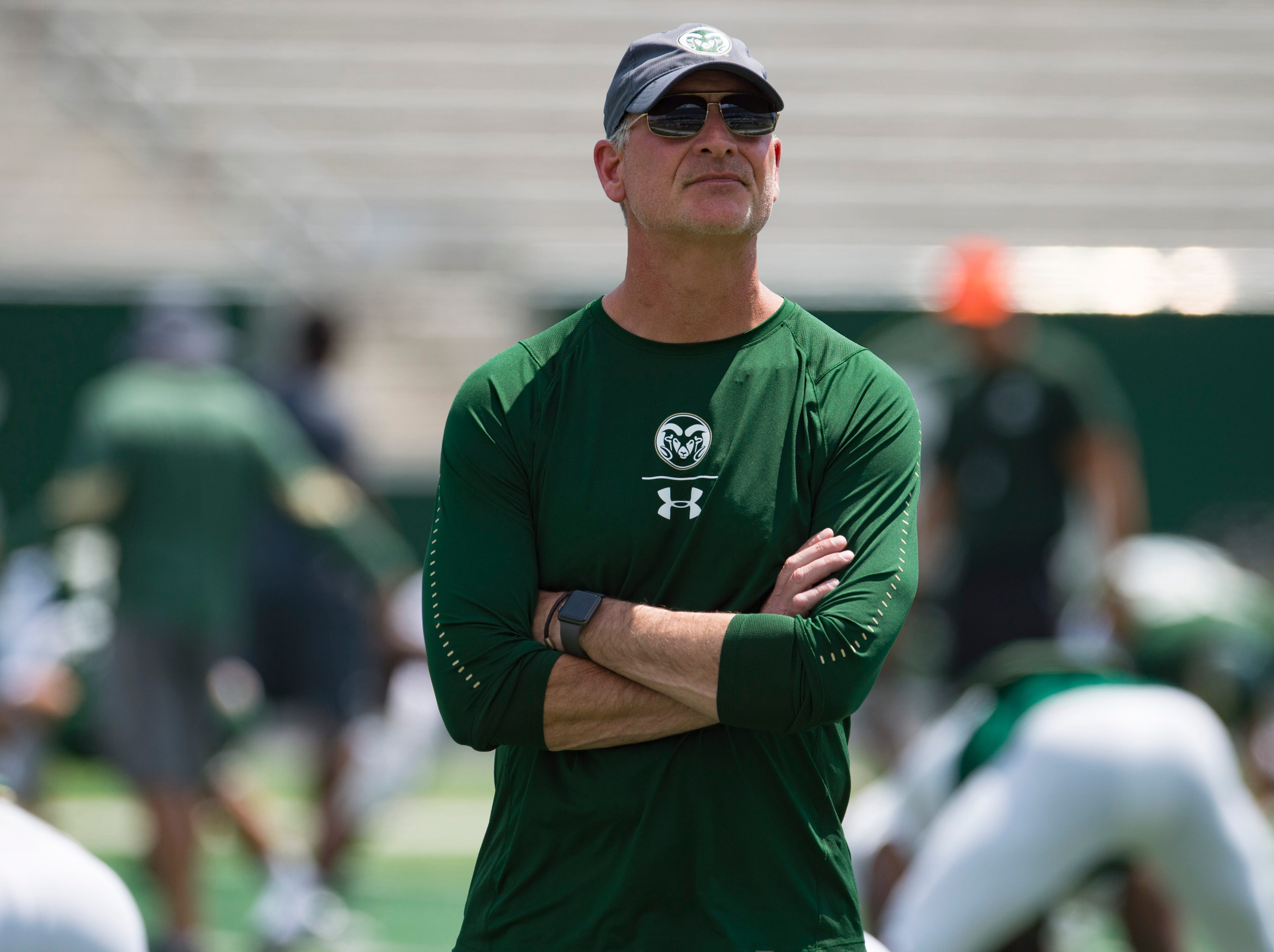 CSU defensive coordinator John Jancek watches the Rams warm up for a scrimmage during an open house hosted by the Rams outside of Canvas Stadium on Saturday, August 4, 2018.